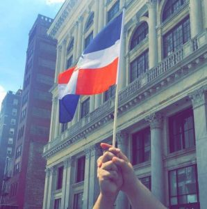 Dominican Flag Being held by two hands on NYC street