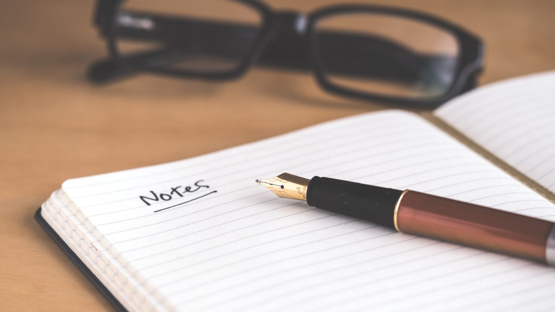notepad, pen and glasses
