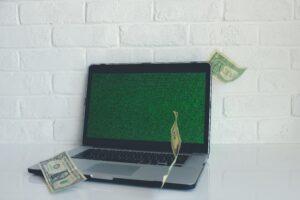 laptop with bills flying around