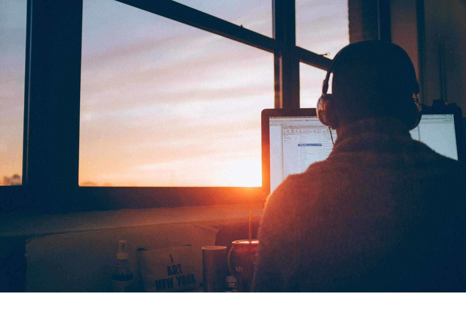 student sitting in front of computer screen in from of a window though which the sun is setting